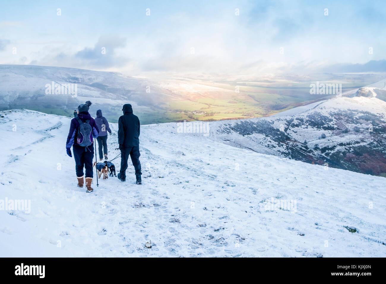 Paseos de invierno. Un grupo de caminantes con perros de caminar en la nieve en la Gran Ridge, Derbyshire Peak District, Imagen De Stock