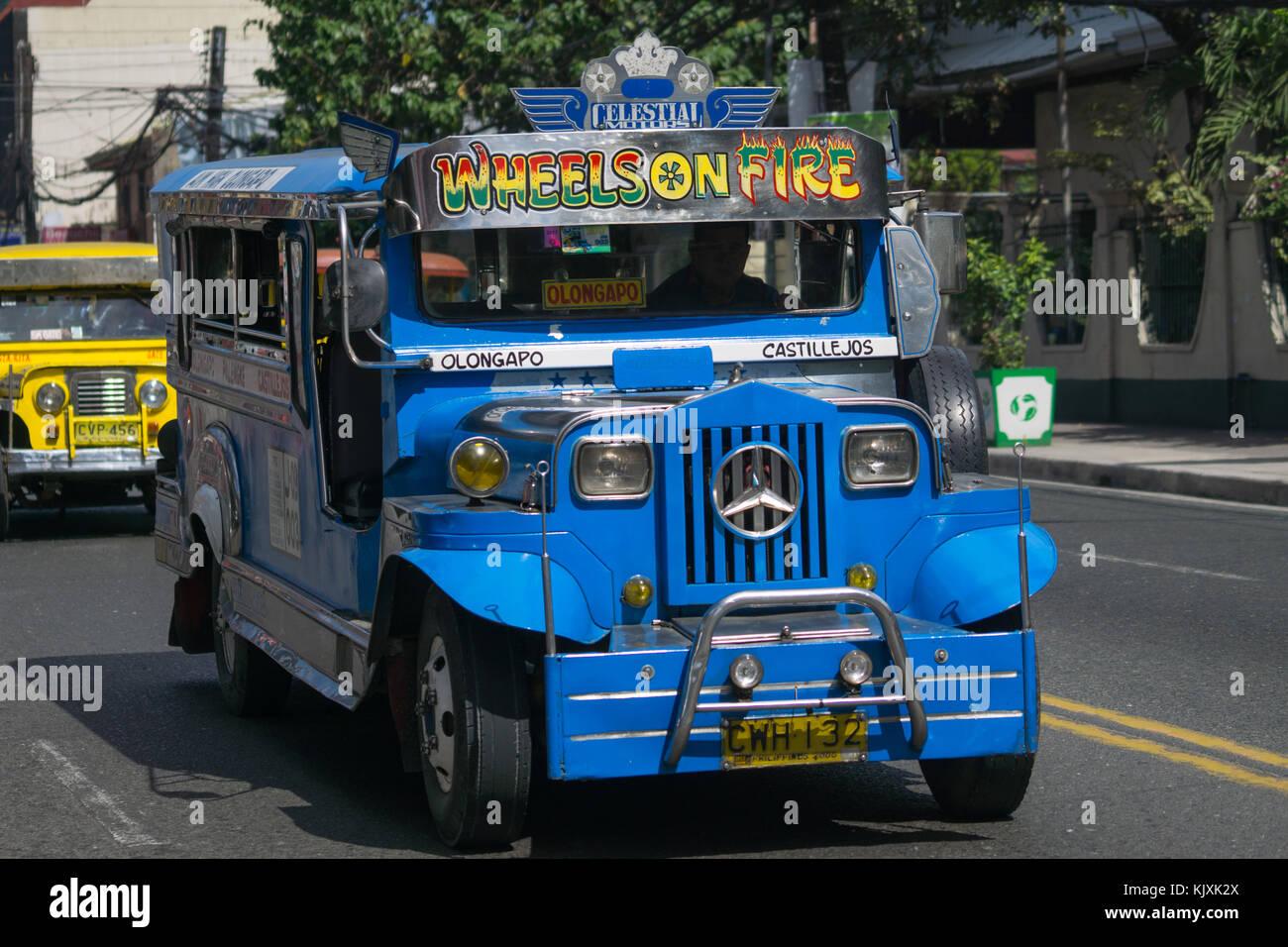 Un jeepney Utilidad Pública azul con el vehículo circulando en la ciudad de Olongapo,Bataan, Filipinas Foto de stock