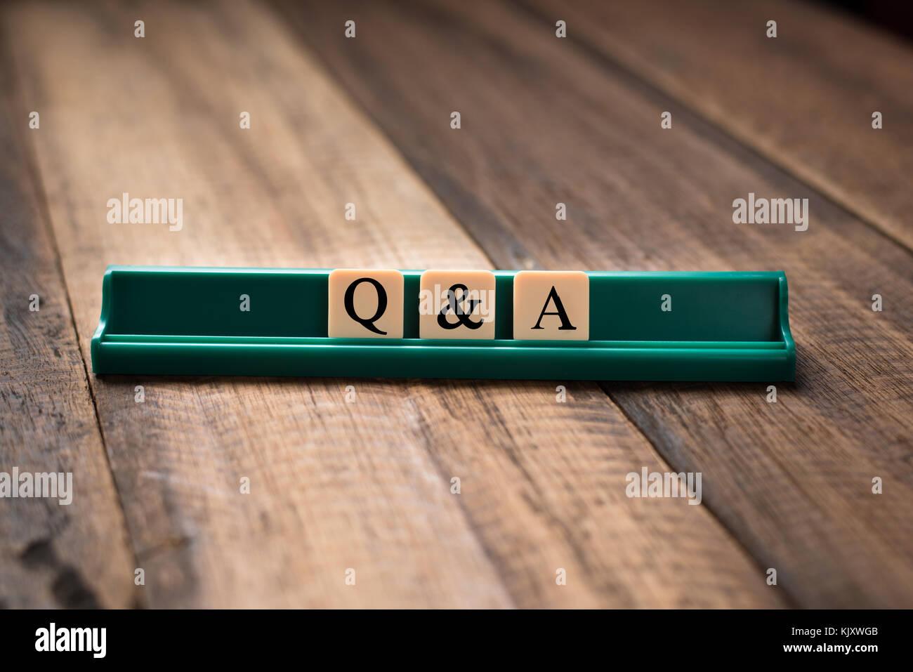Queations y respuestas P&un concepto. q&una letra del alfabeto en azulejos en mesa de madera Imagen De Stock