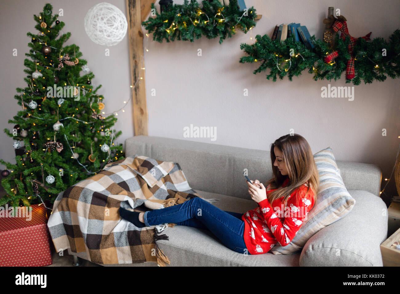 Niña feliz viendo el contenido de streaming en línea en un teléfono inteligente sentado en un sofá Imagen De Stock