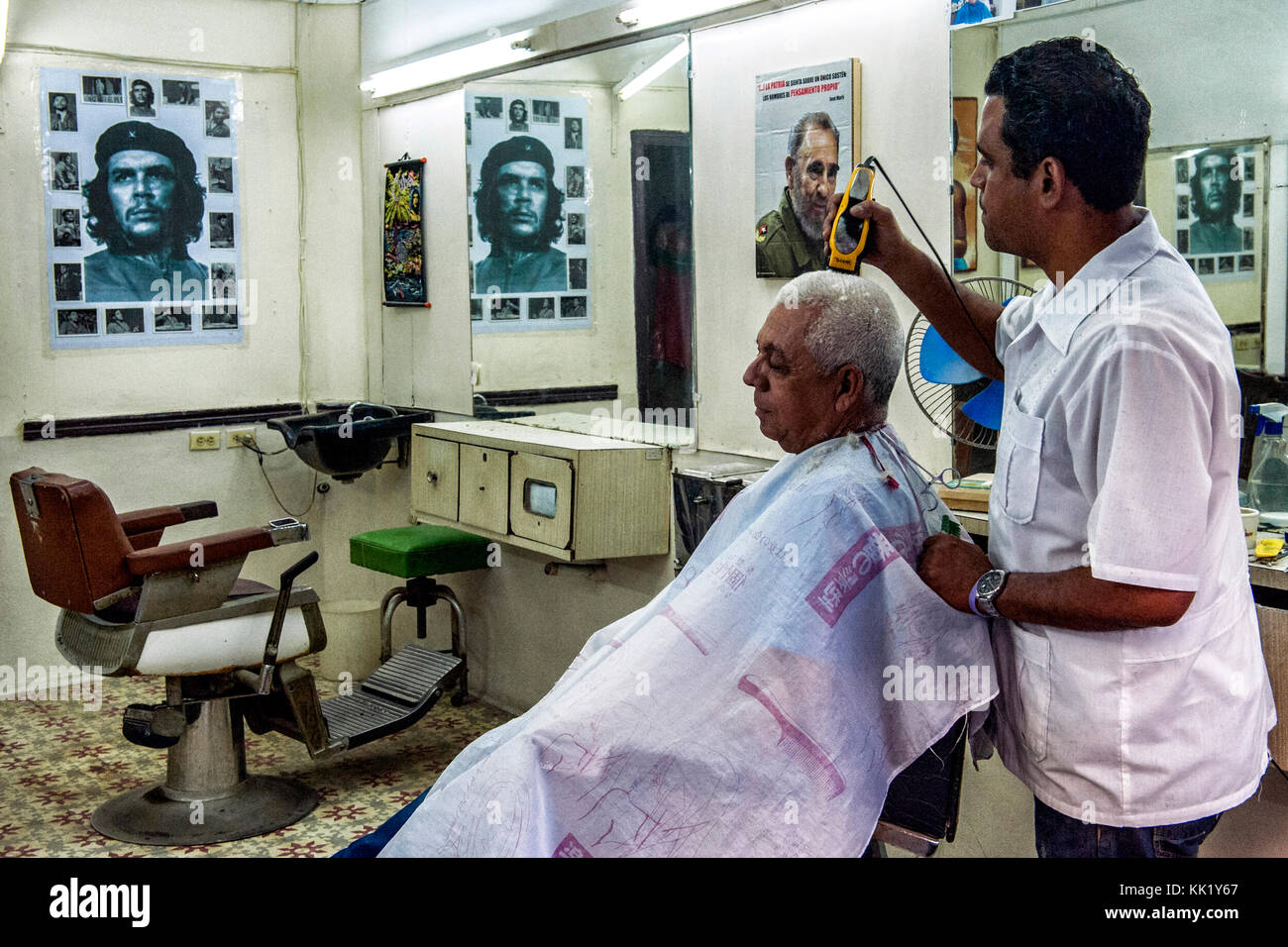 Un peluquero cortando el pelo a un cliente con la afeitadora eléctrica en  una tienda llena 28fc8590fad0