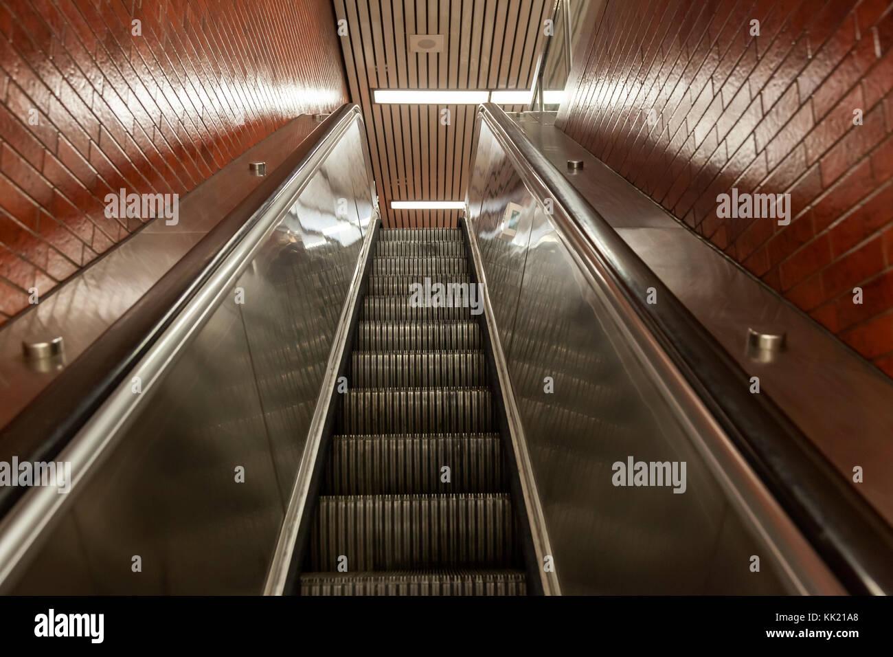 Escalera mecánica subiendo escaleras en una estación de metro Imagen De Stock