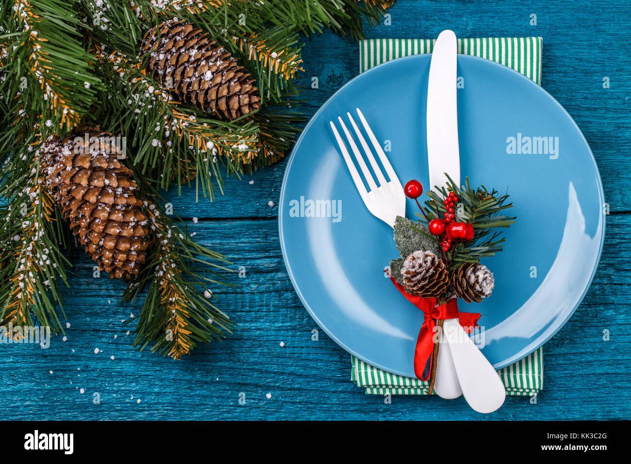 Tabla de Navidad place setting - tabla azul con verde servilleta, placa azul, blanco tenedor y cuchillo, decorado Imagen De Stock