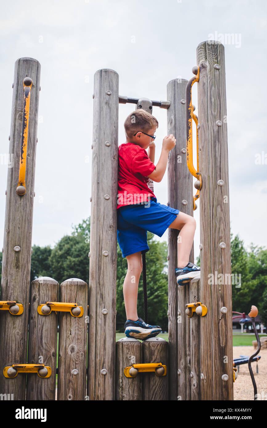 Un niño juega en el equipo de recreo en un día de verano Imagen De Stock