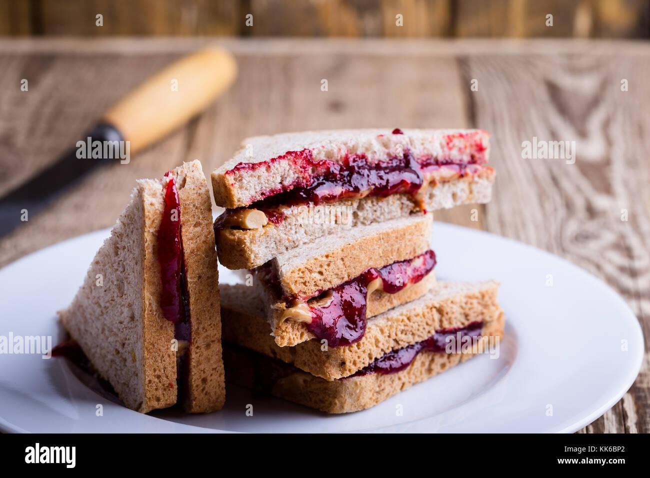 Sándwich de mantequilla de maní y mermelada con pan de trigo entero sobre mesa de madera rústica Imagen De Stock