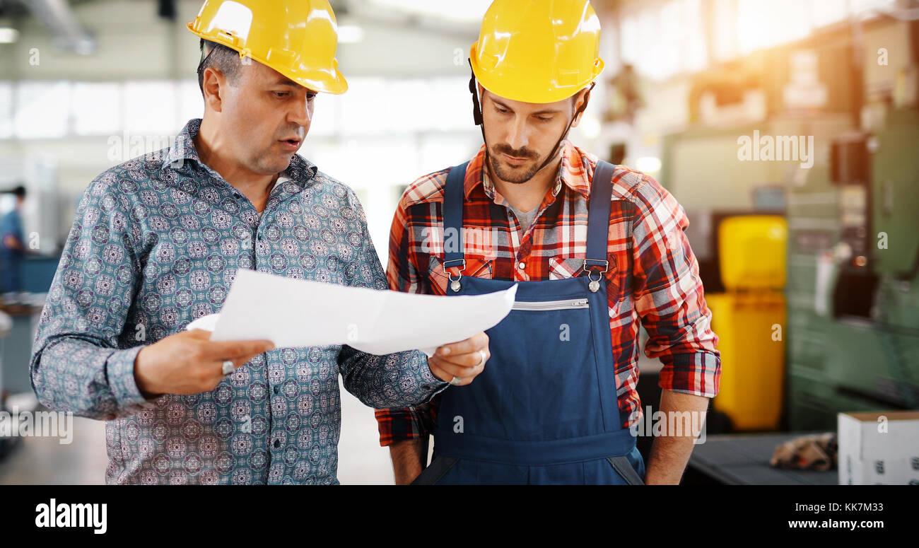 Equipo de ingenieros tras el debate en la fábrica. Imagen De Stock