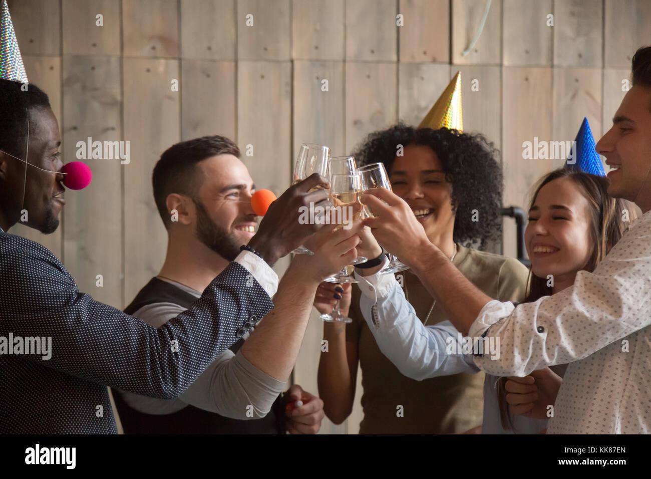 Jóvenes amigos africanos y caucásicos vasos tintineo celebrando Imagen De Stock