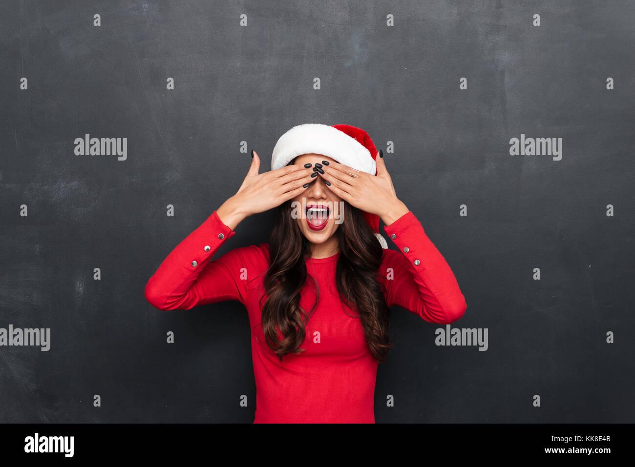 a27eac6d2763b Gracioso mujer morena en una blusa roja y sombrero de navidad con boca  abierta cubriendo sus ojos sobre fondo negro