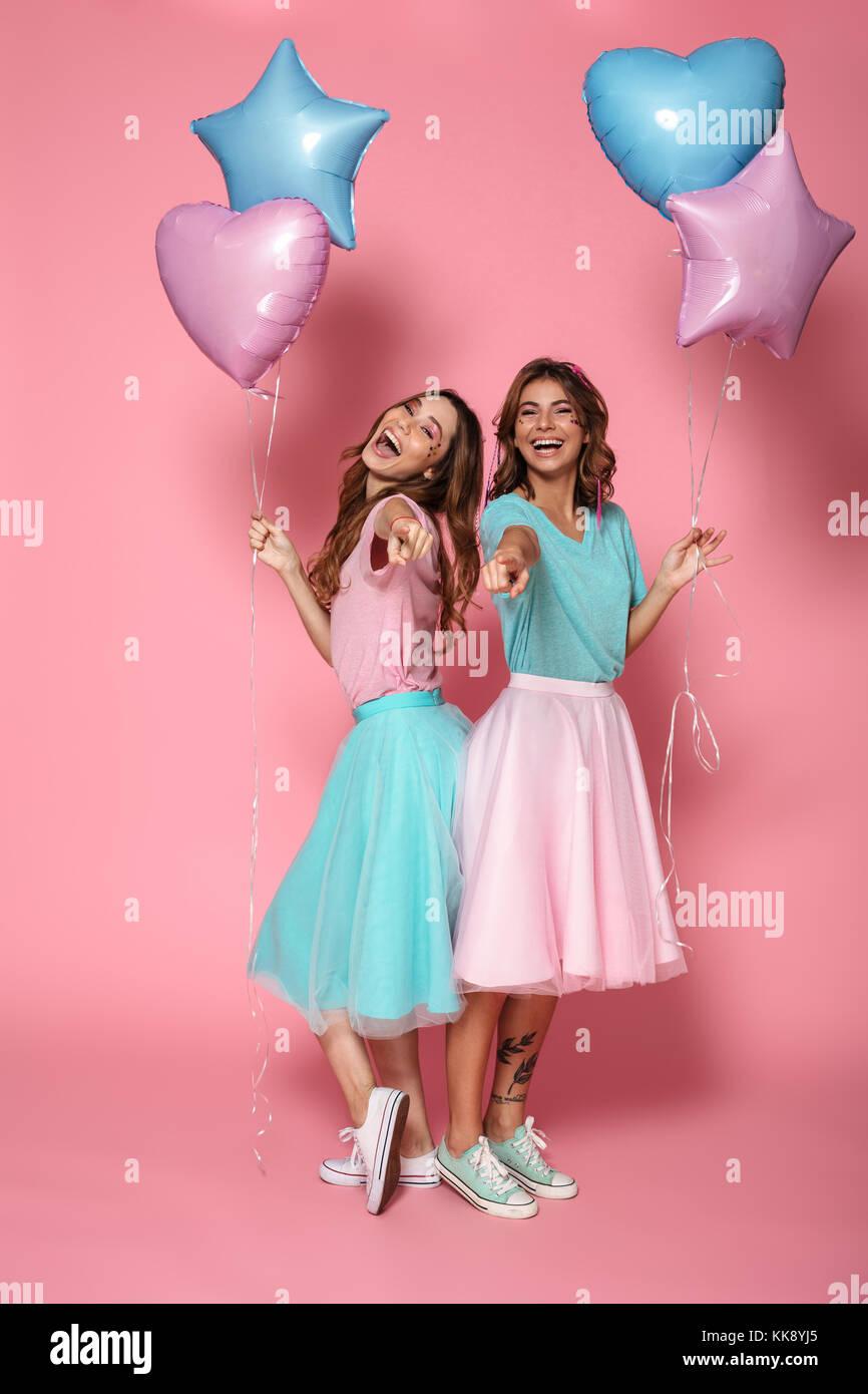 928c9335e ... vestidas con ropa de colores brillantes sosteniendo los globos de aire  mientras está de pie y señalando con el dedo a la cámara aislada sobre rosa  ...