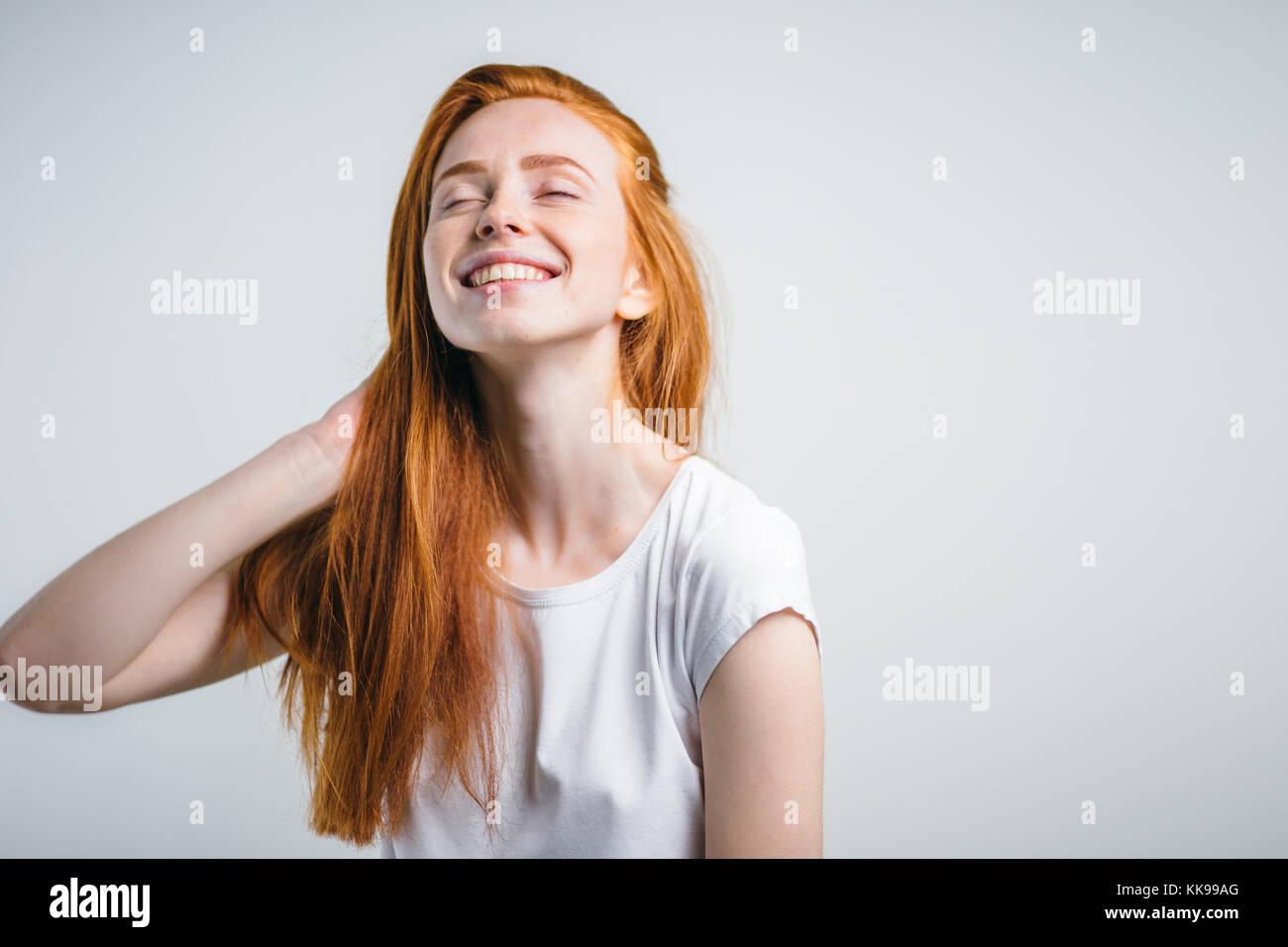 Chica con pecas sonriendo con los ojos cerrados tocando su pelo rojo Imagen De Stock