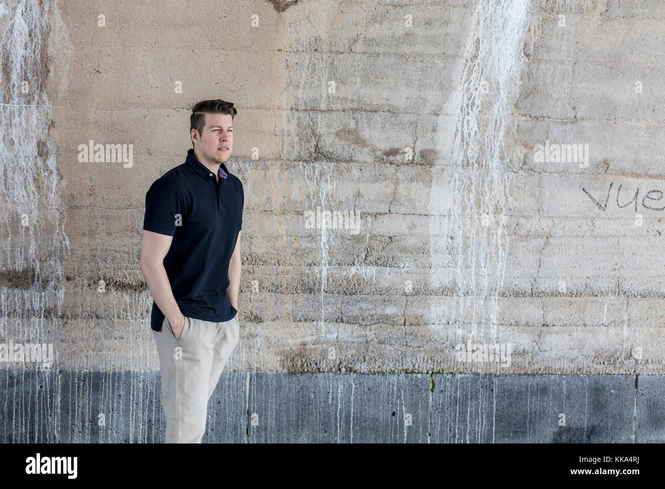 Un hombre vestido casualmente de pie detrás de una pared de color beige. Tres cuartos de longitud. Imagen De Stock