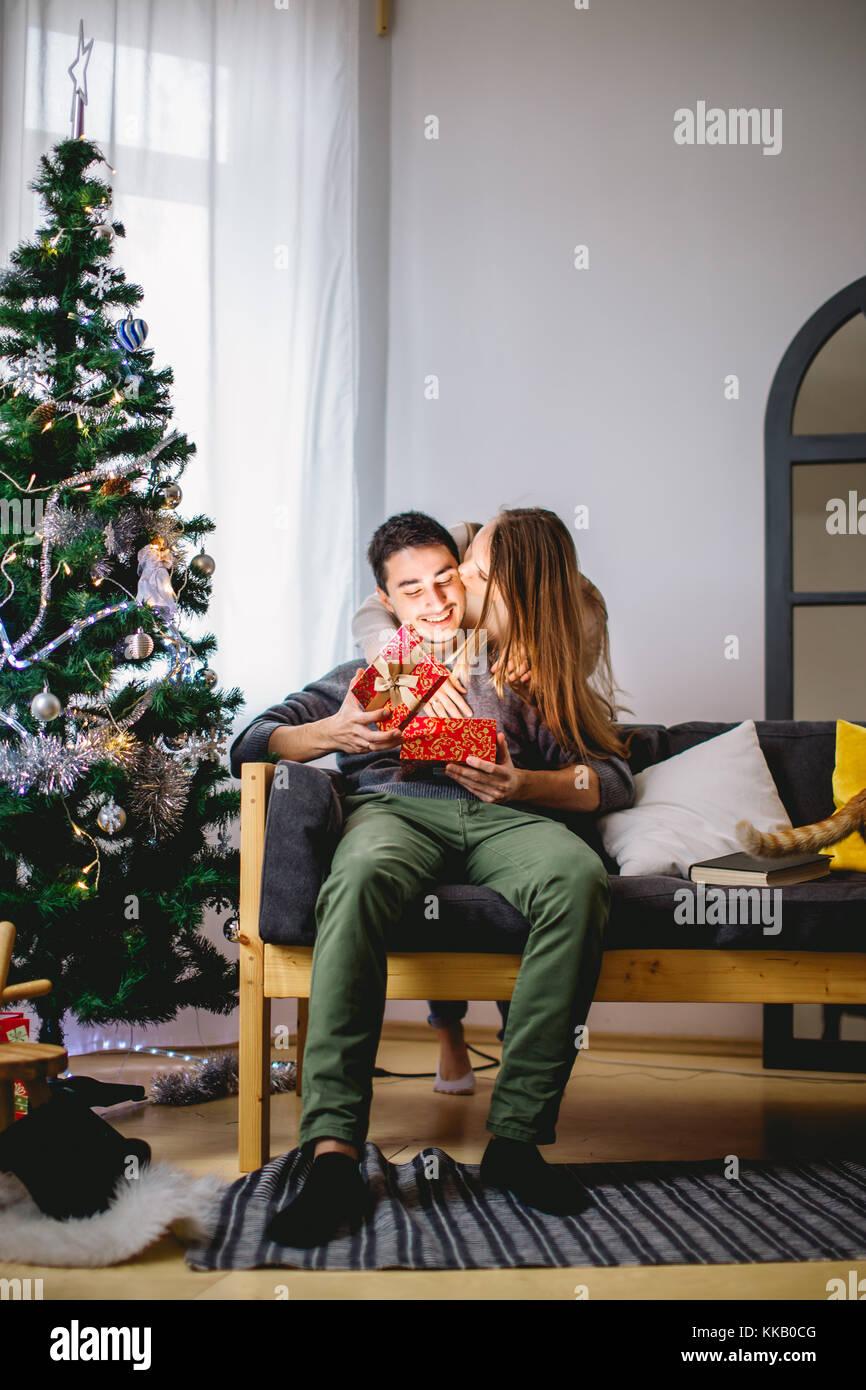 El hombre abre una caja de regalo mientras su novia sentados cerca de ella en el sofá Imagen De Stock