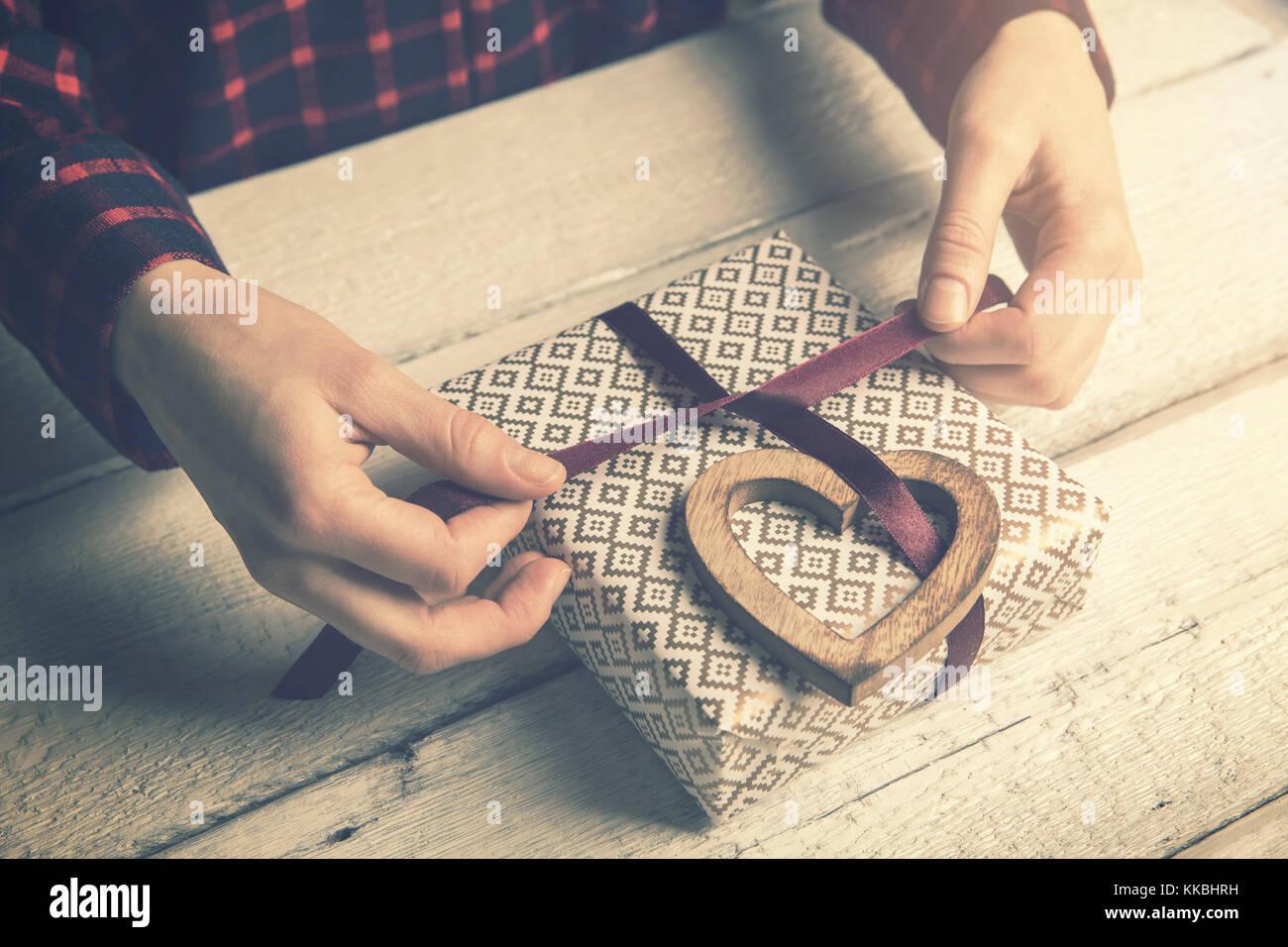 Envolver un regalo para la mujer amada. cinta de atar a un arco de madera con decoración de corazón Imagen De Stock