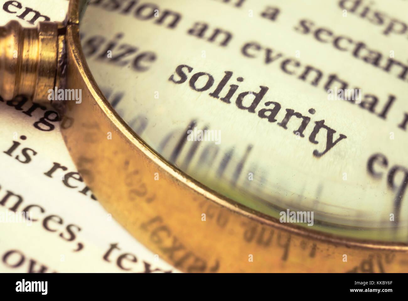 """La palabra """"solidaridad"""" destacó por una lupa y envuelto con texto borroso. Imagen De Stock"""
