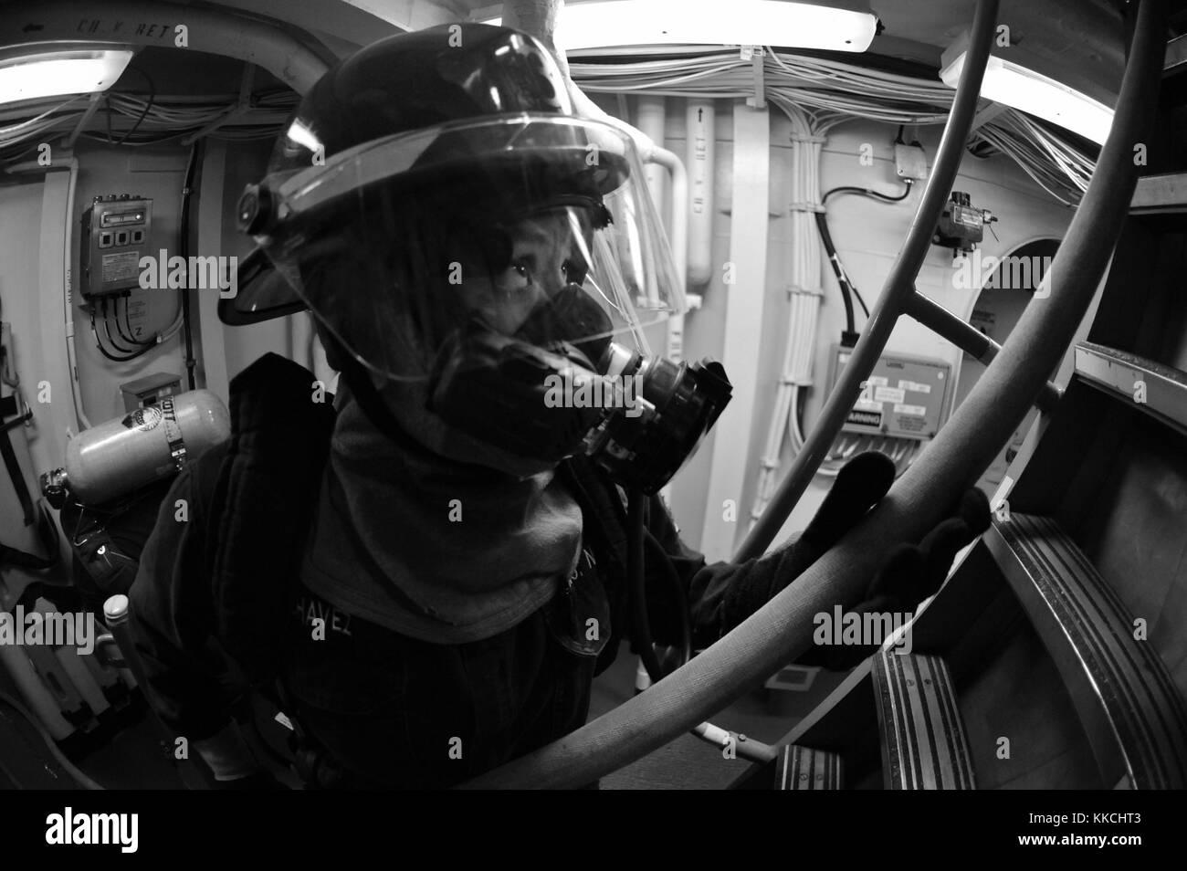 Sistema de turbina de gas técnico bombero mecánico isabel Chávez, asignado a la clase Arleigh Burke de misiles guiados destructor USS mccampbell ddg 85, pasa por una manguera de incendios a los marineros luchando contra un incendio simulado durante un taladro de control de daños, el mar de Japón. Imagen cortesía de especialista en comunicación de masas seaman declan barnes/us navy. 2012. Foto de stock