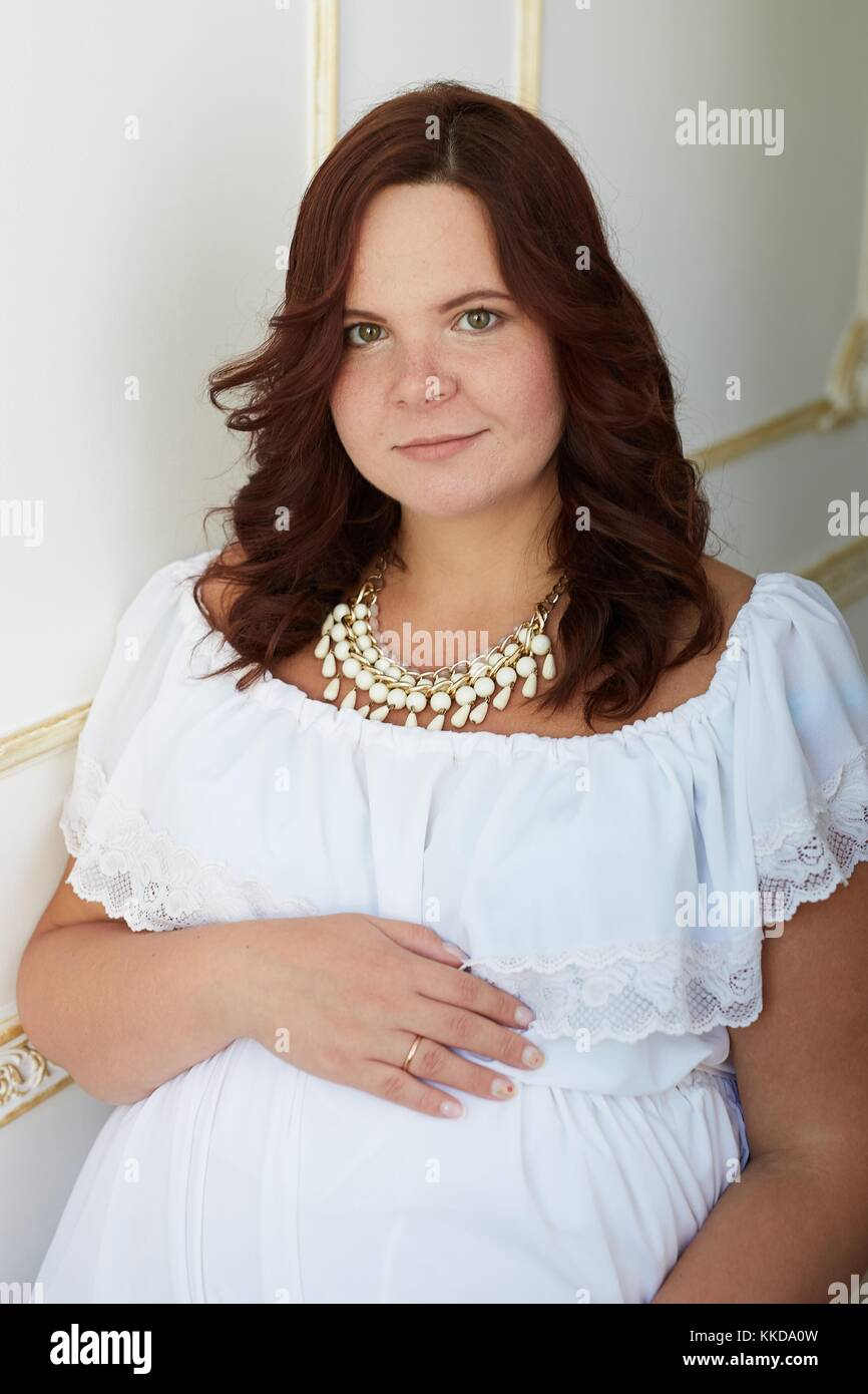 67c27cfdf Hermosa mujer embarazada con sonrisa feliz y apacible rostro vestida de  blanco puro vestido y joyas