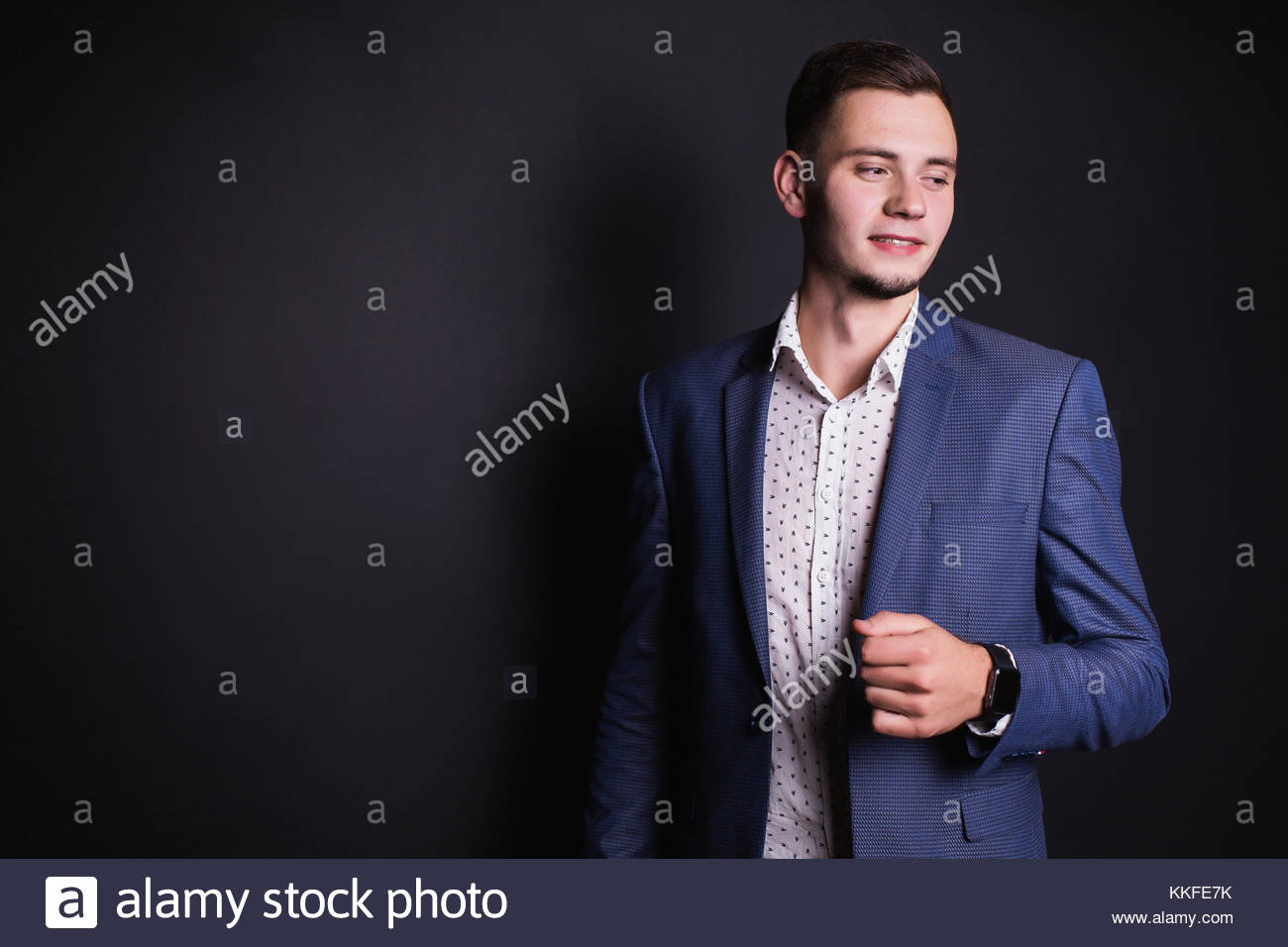 Joven empresario exitoso en traje y camisa blanca y elegante reloj en mano  sobre un fondo negro. El hombre elegante. Profesiones para hombres 84c7596aefb