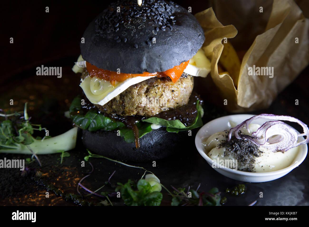 Hamburguesa de cordero servido con un bollo de pan negro en el restaurante mute en Riga, Letonia. la hamburguesa Imagen De Stock