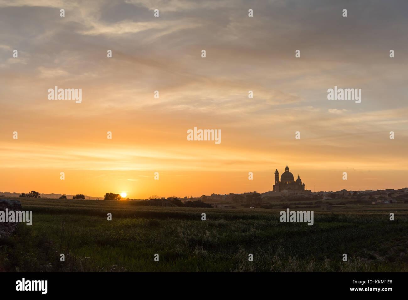 Puesta de sol detrás de la Basílica de San Jorge creando una silueta , Victoria Gozo Malta Europa Foto de stock