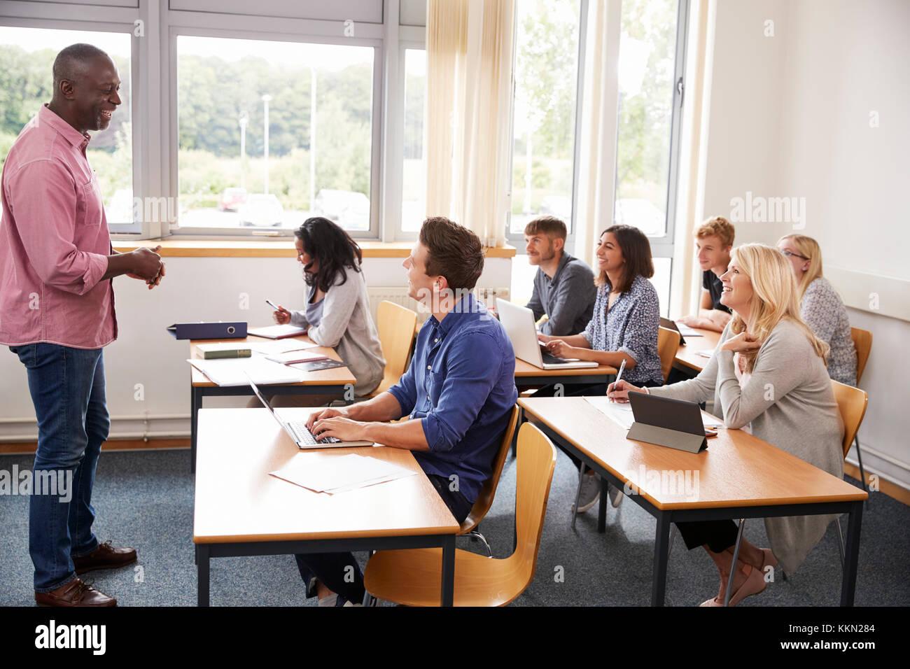Tutor varón dando clase de estudiantes adultos. Foto de stock
