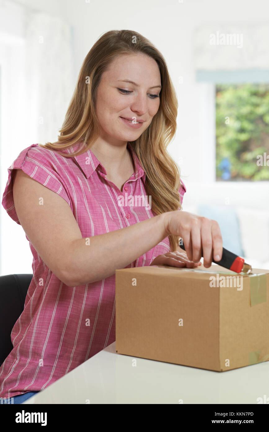 Mujer con cuchillo para Abrir paquete en casa Imagen De Stock