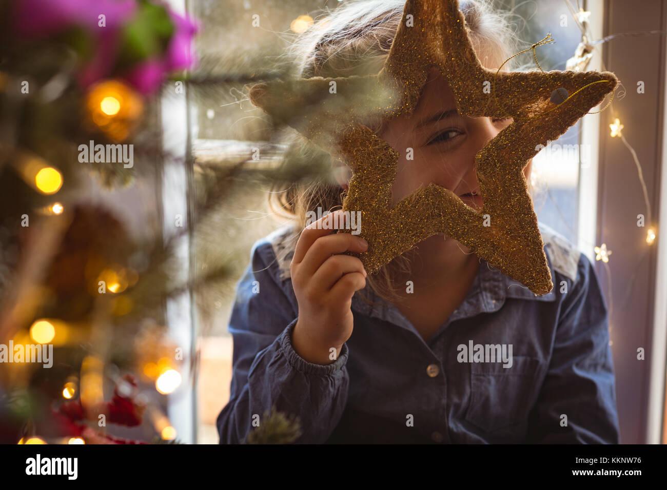 Chica busca parado cerca del árbol de navidad y mirando a través de la estrella Imagen De Stock