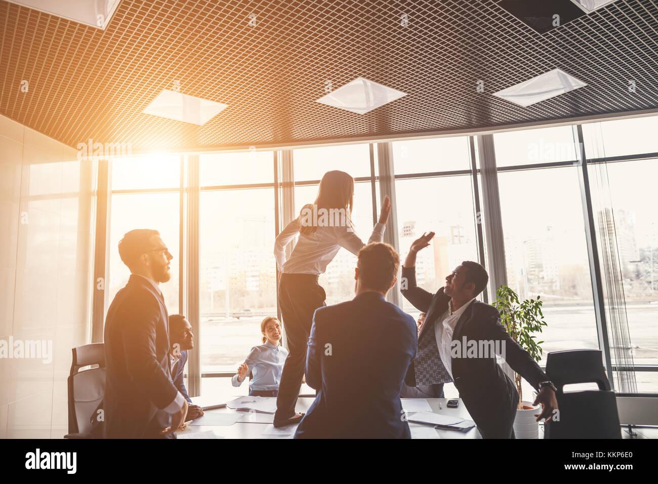 Gente de negocios dando de alta cinco mientras sus colegas mirándolos Foto de stock