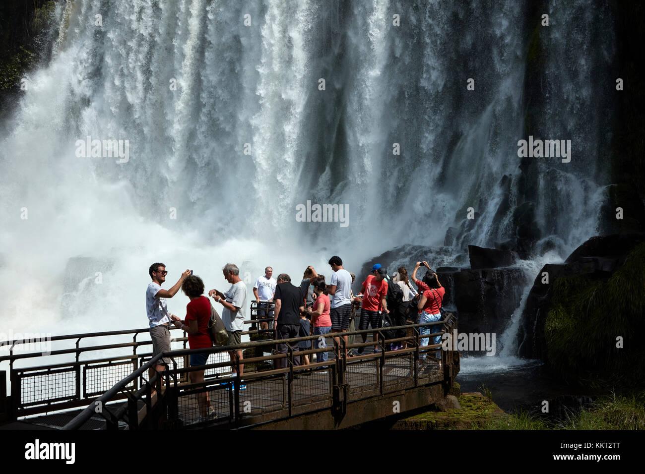 Turistas en observación por las Cataratas del Iguazú, en la frontera Argentina - Brasil, Sudamérica Foto de stock