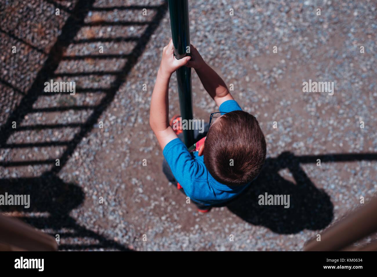 Un niño se desliza hacia abajo por un polo deslizante en un parque. Imagen De Stock