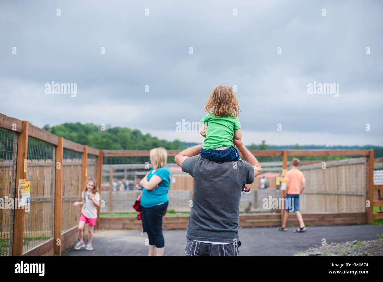 Un padre lleva a su hija sobre sus hombros. Imagen De Stock