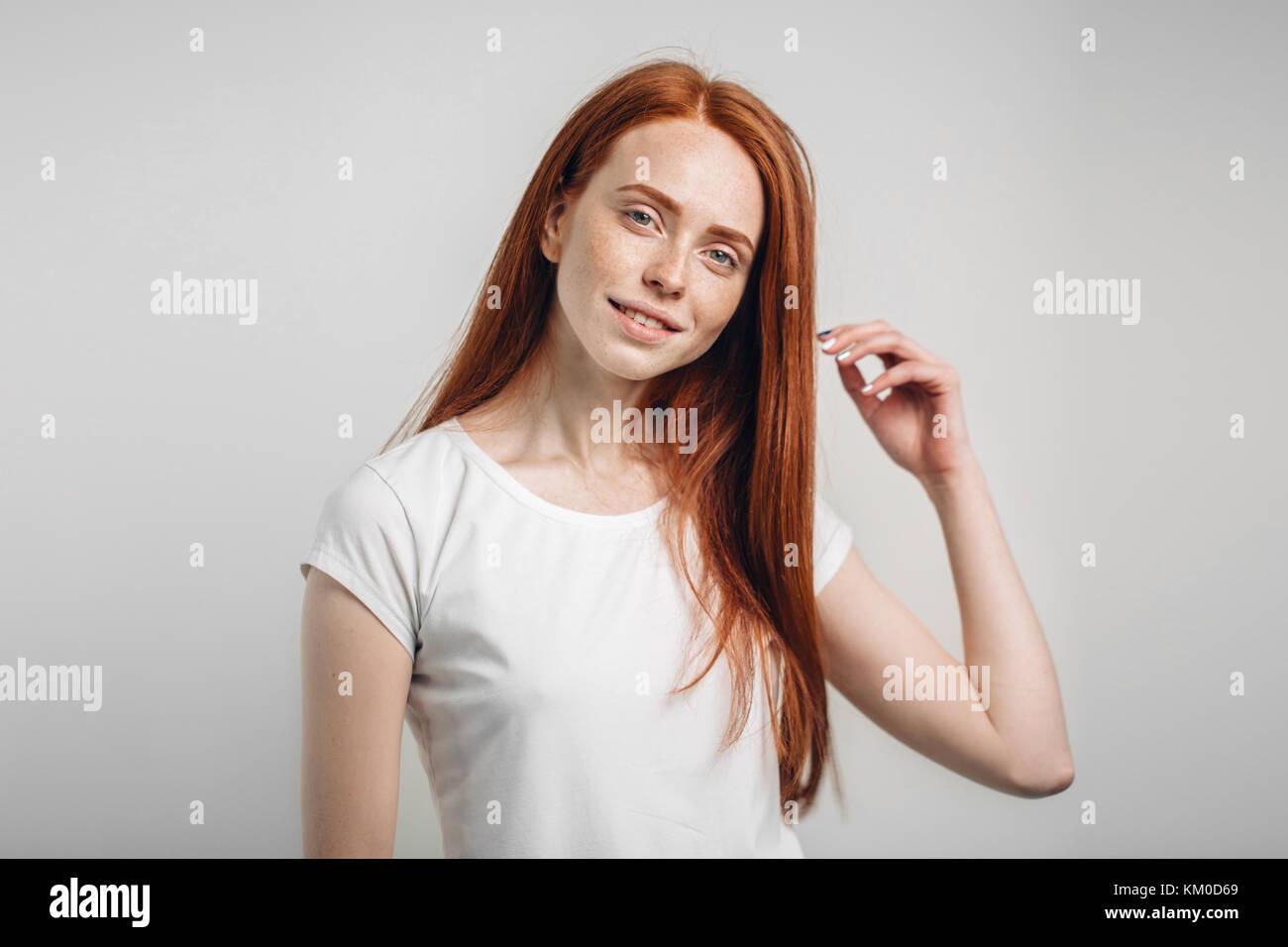 Chica sonriente con los ojos cerrados tocando su pelo rojo sobre fondo blanco. Imagen De Stock