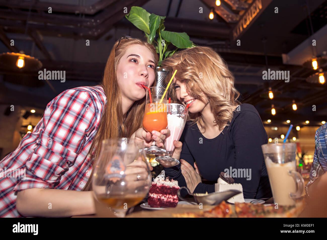 Mujer joven bebiendo malteadas mientras estaba sentado con amigos en el café Imagen De Stock