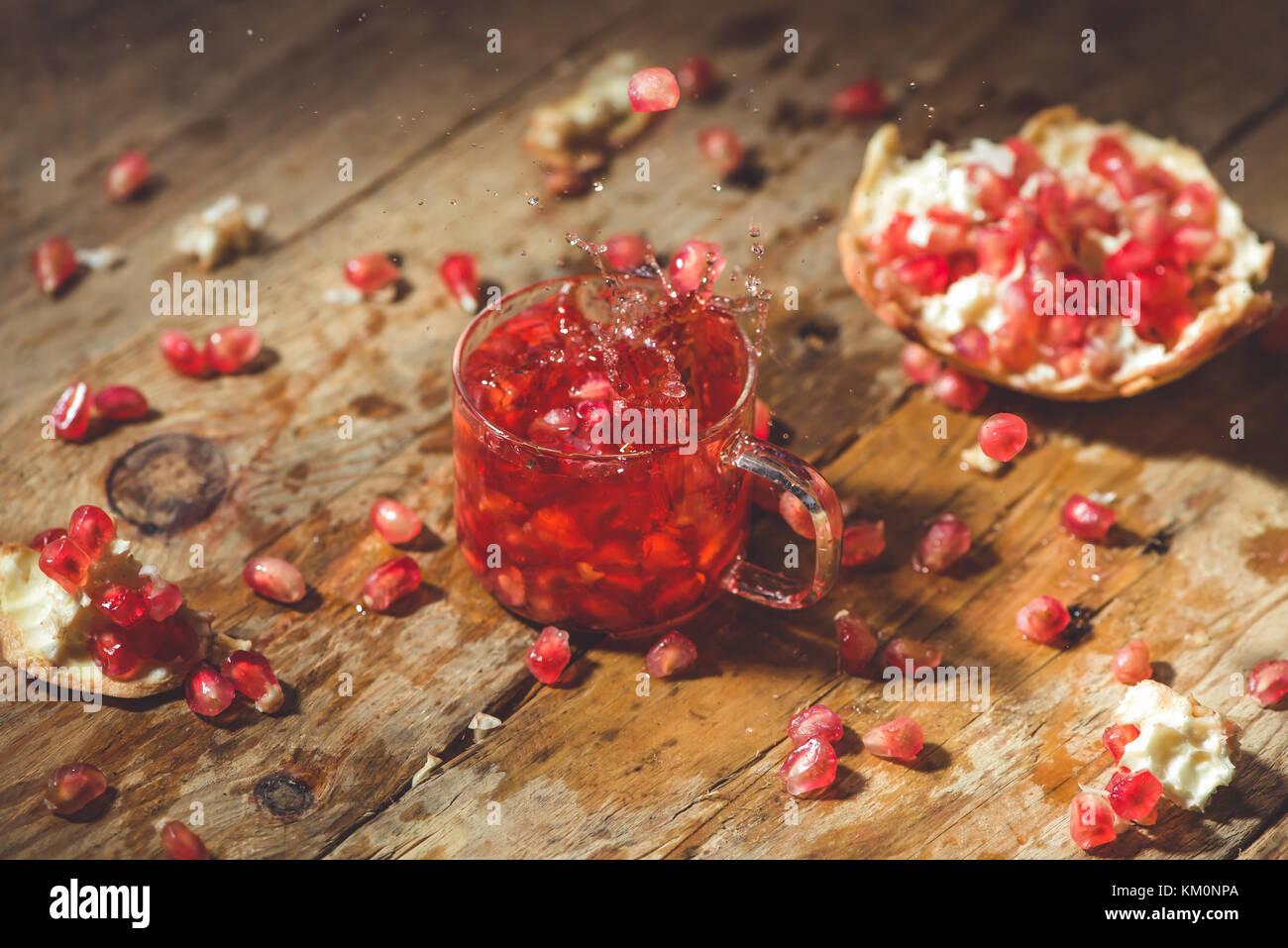 Granada madura con grietas y salpicaduras de zumo de frutas y semillas de fondo vintage de madera. Imagen De Stock