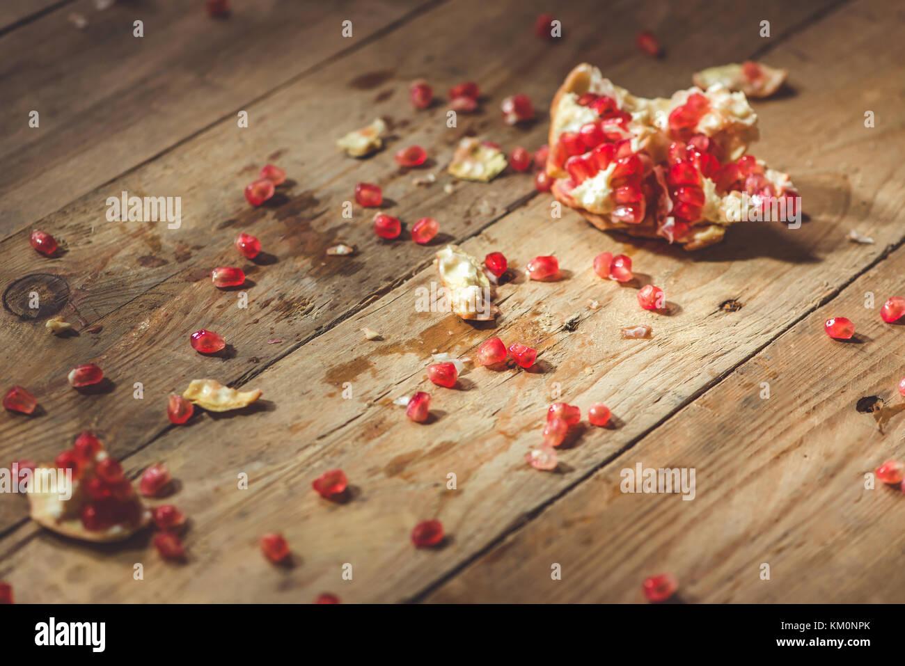 Caída de granada madura con grietas y salpicaduras de zumo de frutas y semillas de fondo vintage de madera. Imagen De Stock