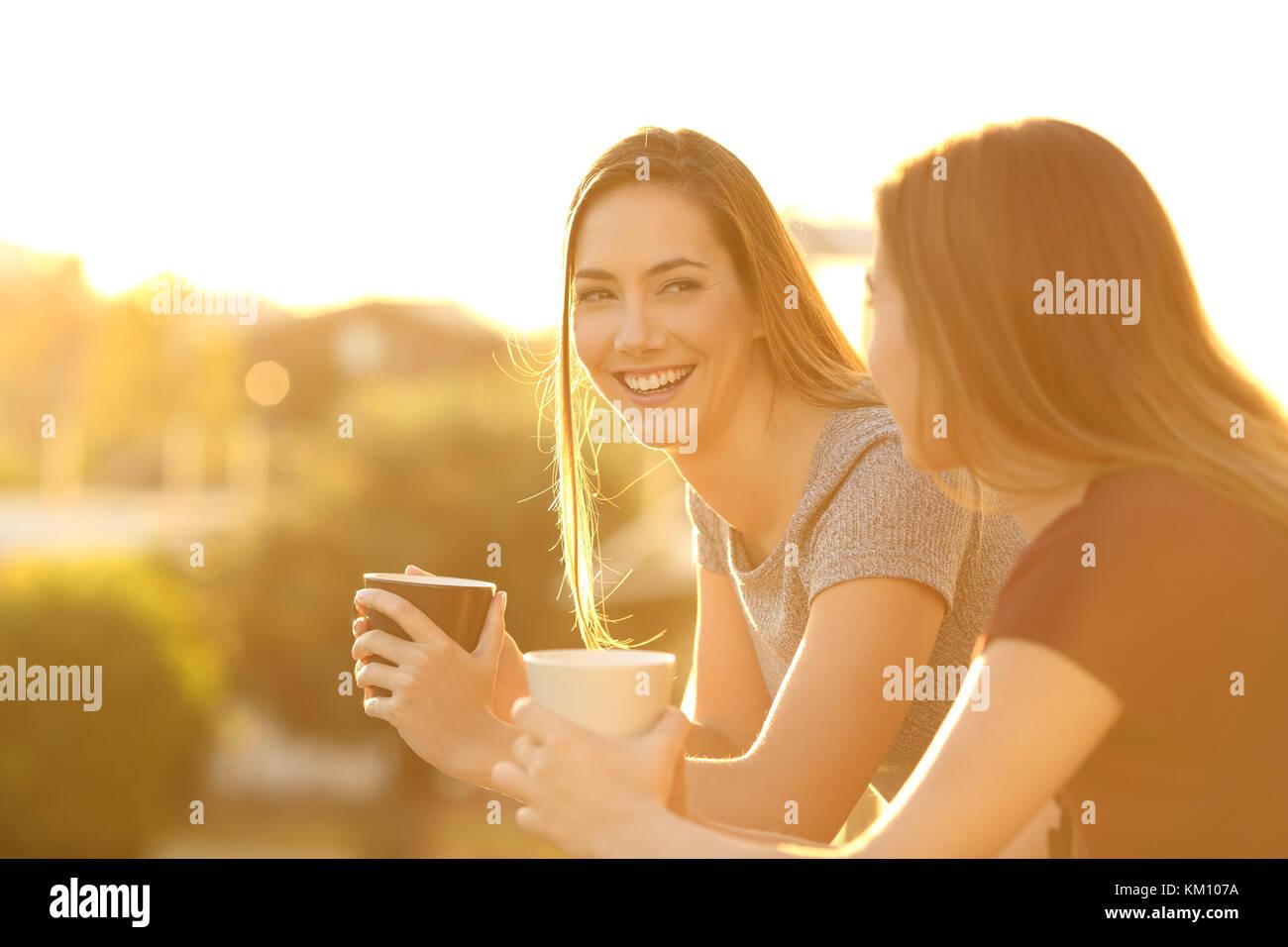 Dos amigos hablando fuera feliz en un balcón de la casa al atardecer Imagen De Stock