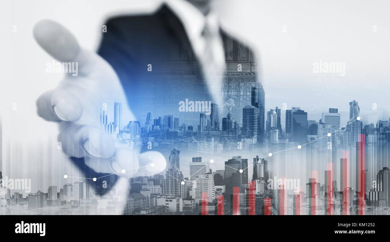 Empresario de doble exposición extendiendo la mano con edificios de la ciudad y elevar el gráfico Imagen De Stock