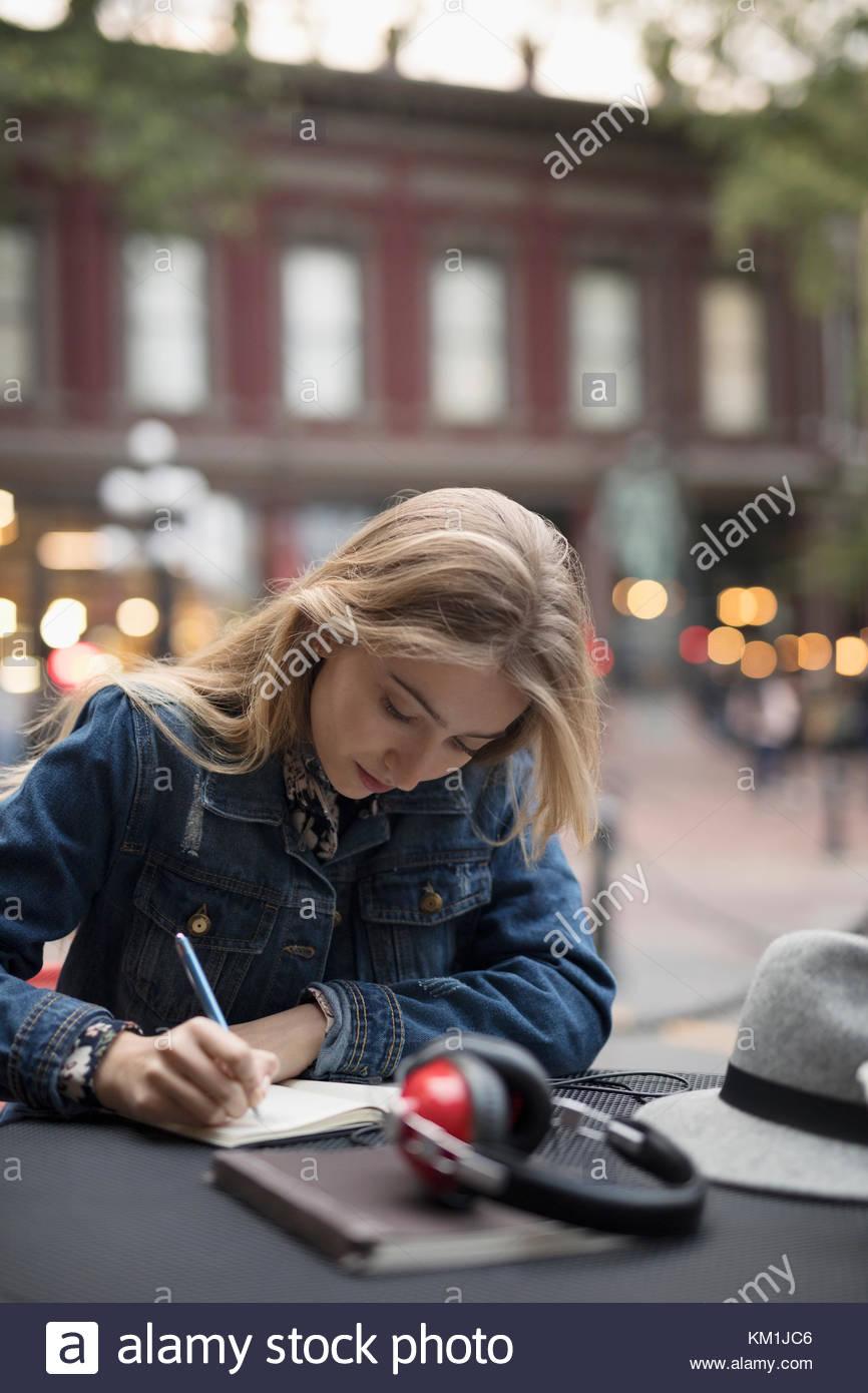 Joven rubia escrito en el diario en la cafetería Imagen De Stock