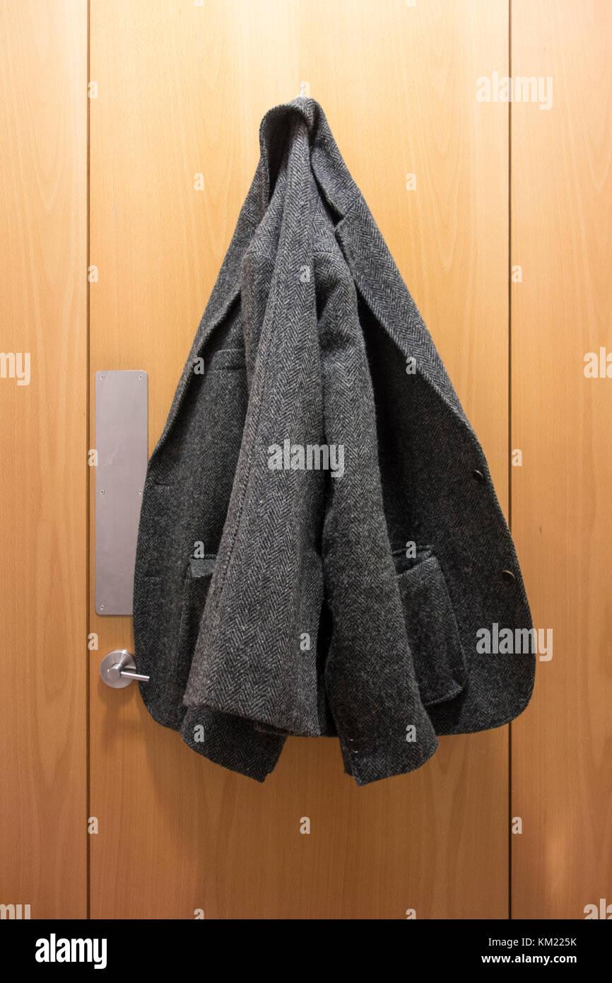 Chaqueta de Tweed colgado en el interior de un inodoro puerta del armario Imagen De Stock