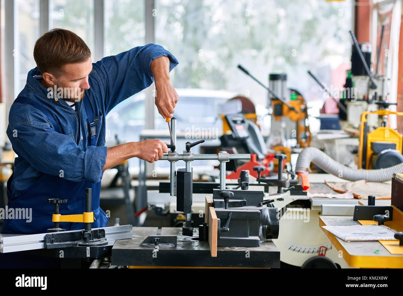 Hombre reparando máquinas en la fábrica Imagen De Stock