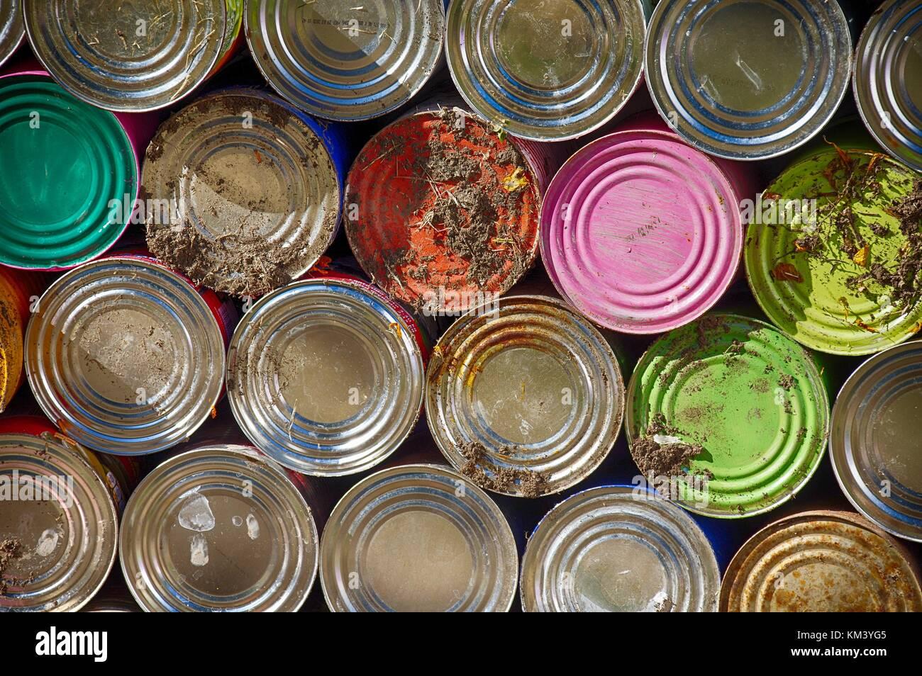 Colorido latas apiladas a lo largo de la pared de un cementerio en México Foto de stock
