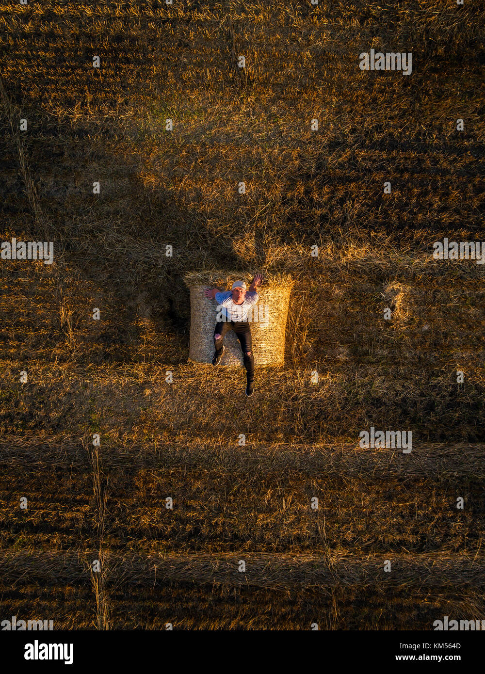 Joven disfruta del sol en la parte superior de una paca de heno Imagen De Stock