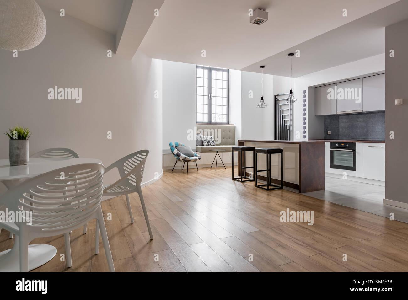 Elegante apartamento con cocina abierta, mesas y sillas blancas Foto ...
