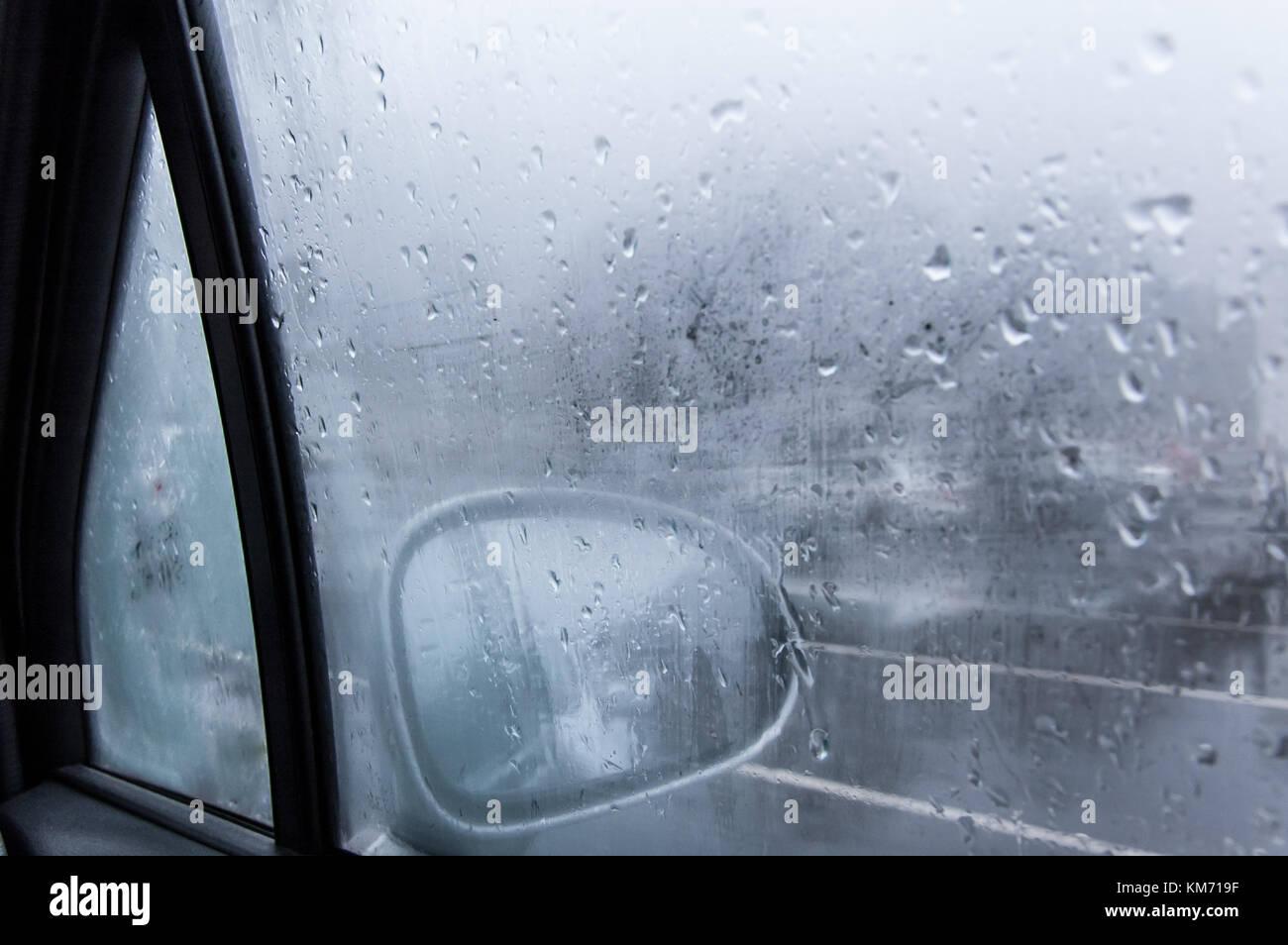Vista de un espejo lateral del coche desde el interior del coche con la condensación y la lluvia en el cristal Imagen De Stock