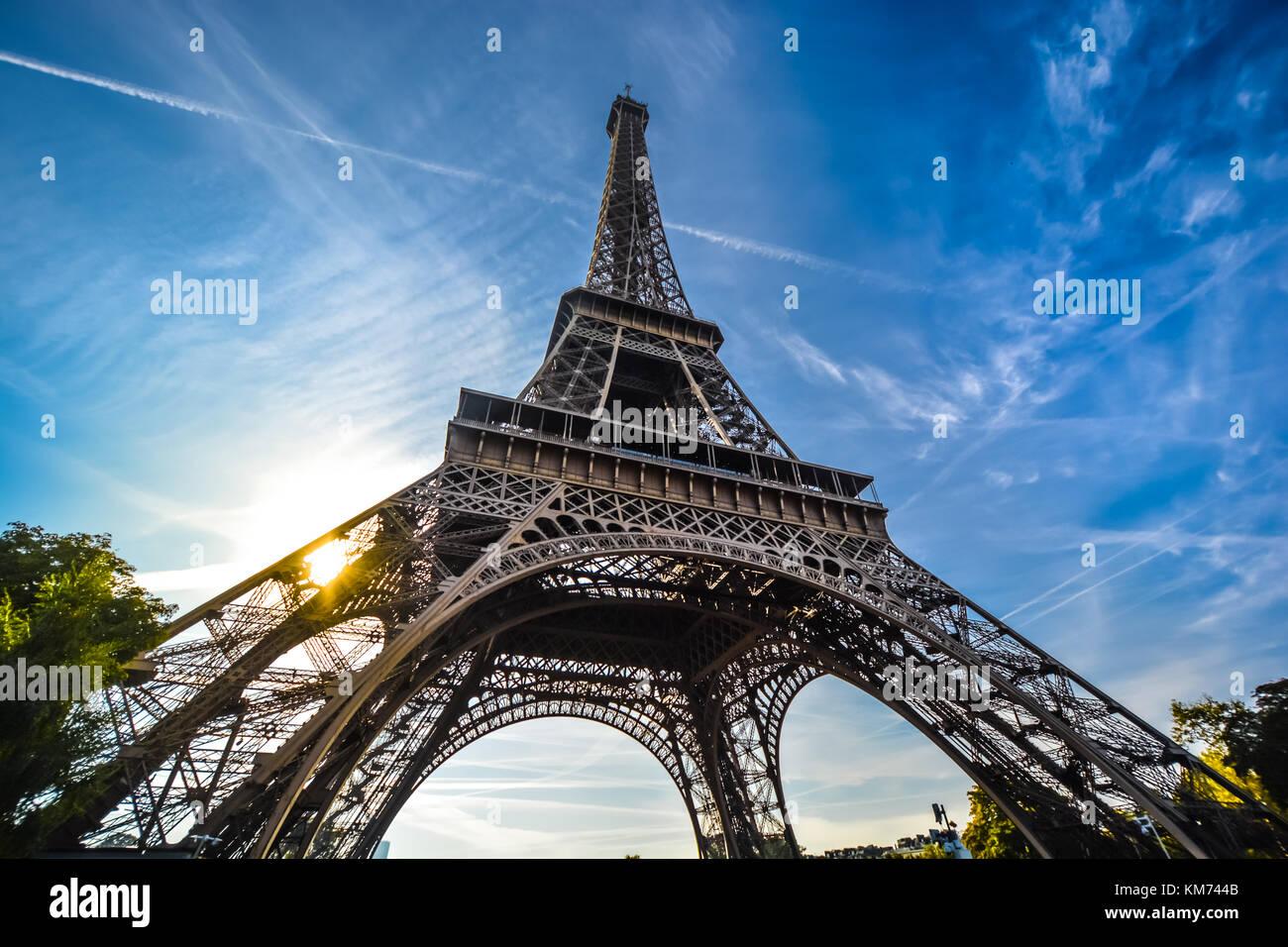 Una vista de la Torre Eiffel con una lente gran angular, mirando hacia arriba desde la base en una tarde soleada Imagen De Stock