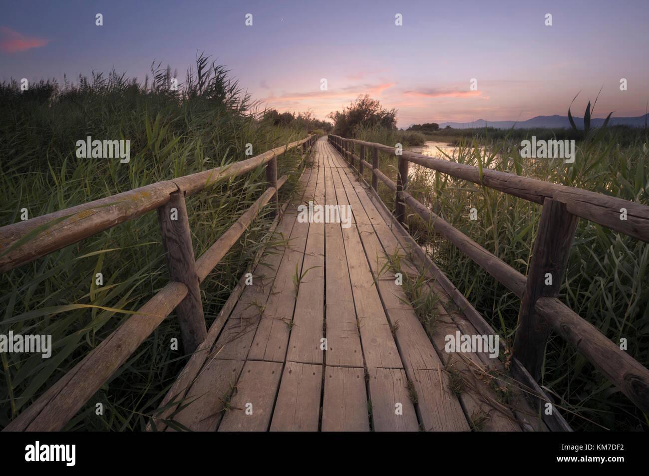 Fotografía artística de un sendero de madera al atardecer en un pantano en la provincia de Alicante, España. Foto de stock