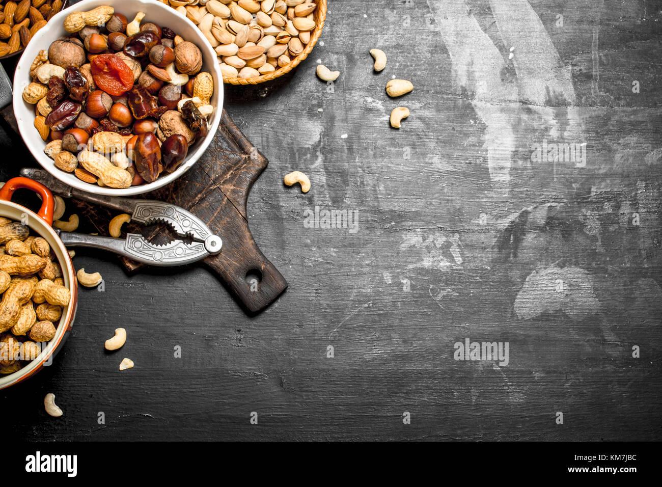 Nueces y frutos secos en un recipiente con un cascanueces. sobre una pizarra negra. Foto de stock