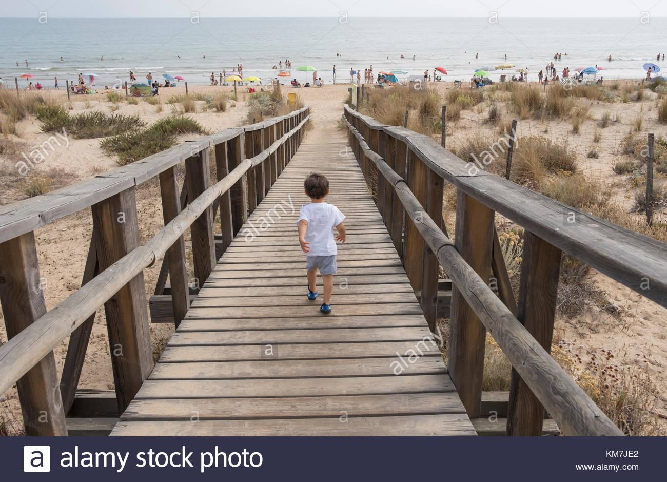 Chico joven corriendo a la playa en la pasarela de madera Imagen De Stock