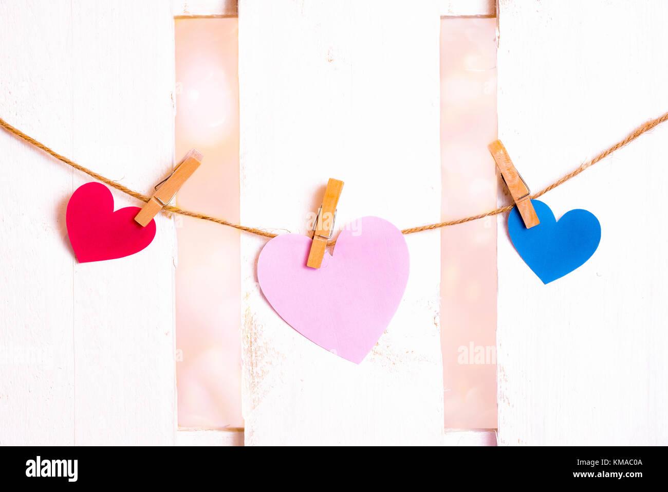 Imagen del día de San Valentín con un gran corazón rosa en el centro, uno rojo y uno azul en los lados, hecho de papel y atado a una cadena con pinzas de madera Foto de stock