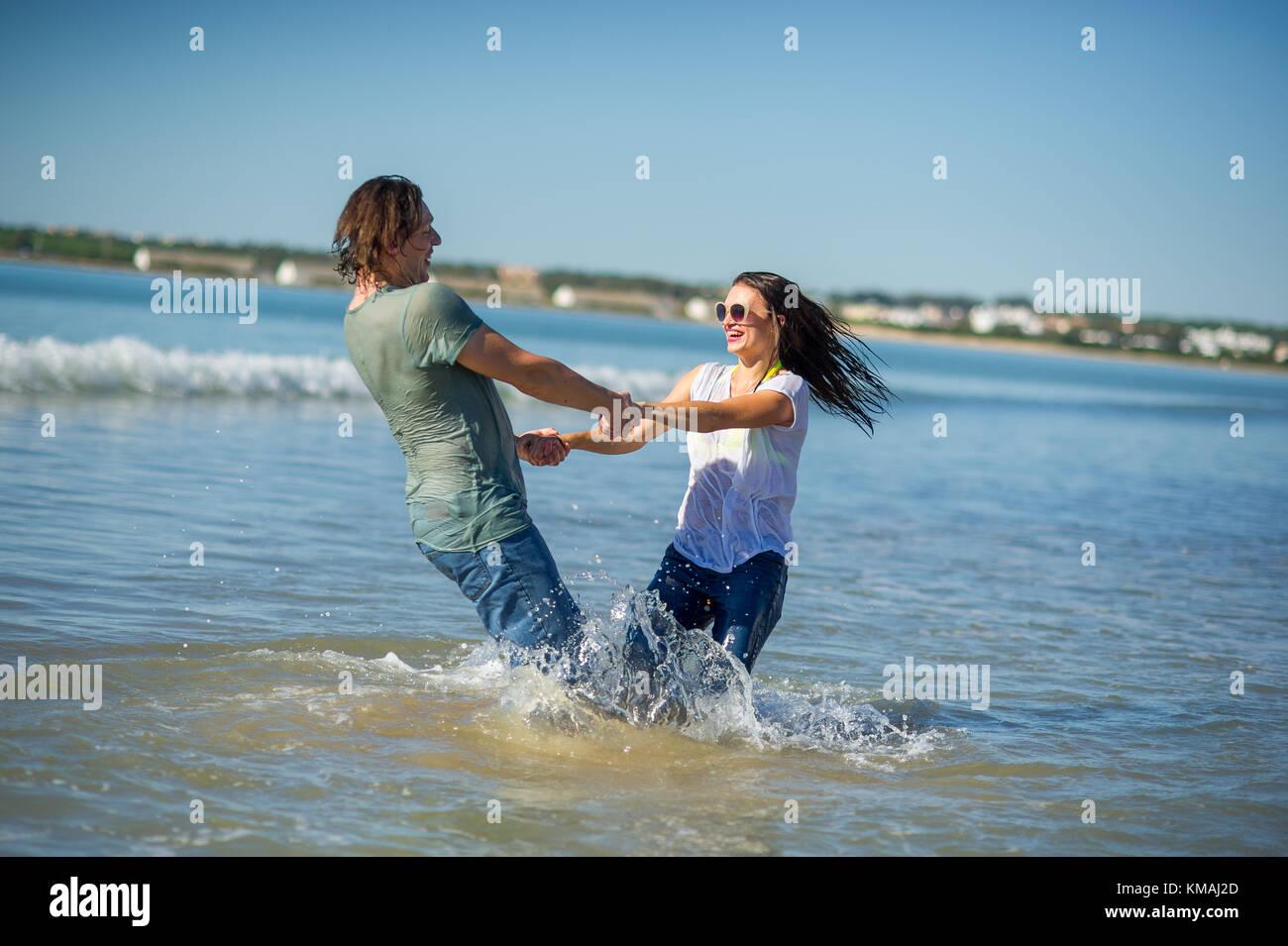 6e84d7f35 Feliz pareja joven baila en el mar. La ropa mojada y cabello. El mar