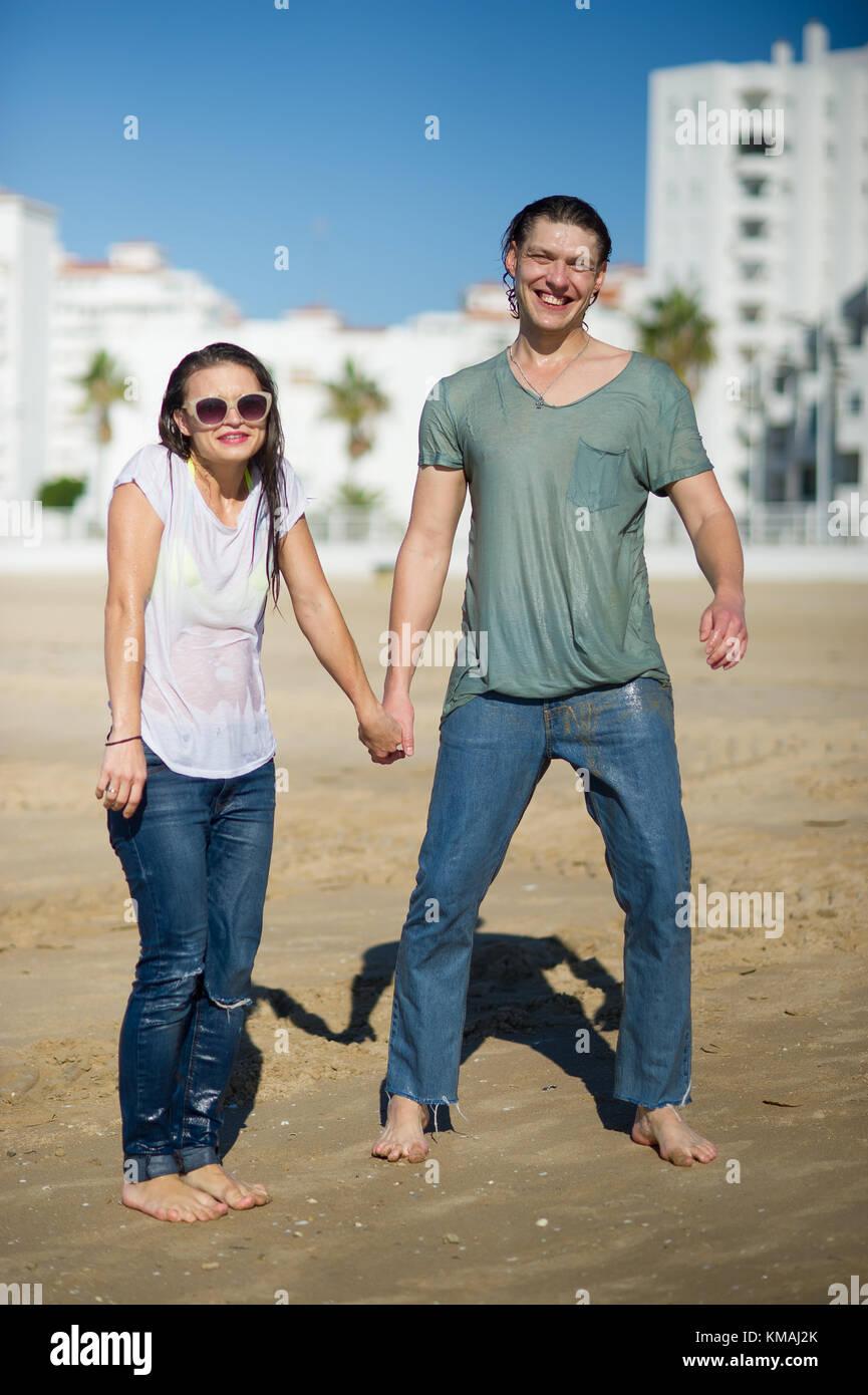 7685bf920 Alegre pareja joven se encuentra en la ropa húmeda en la playa. guy tiene  una